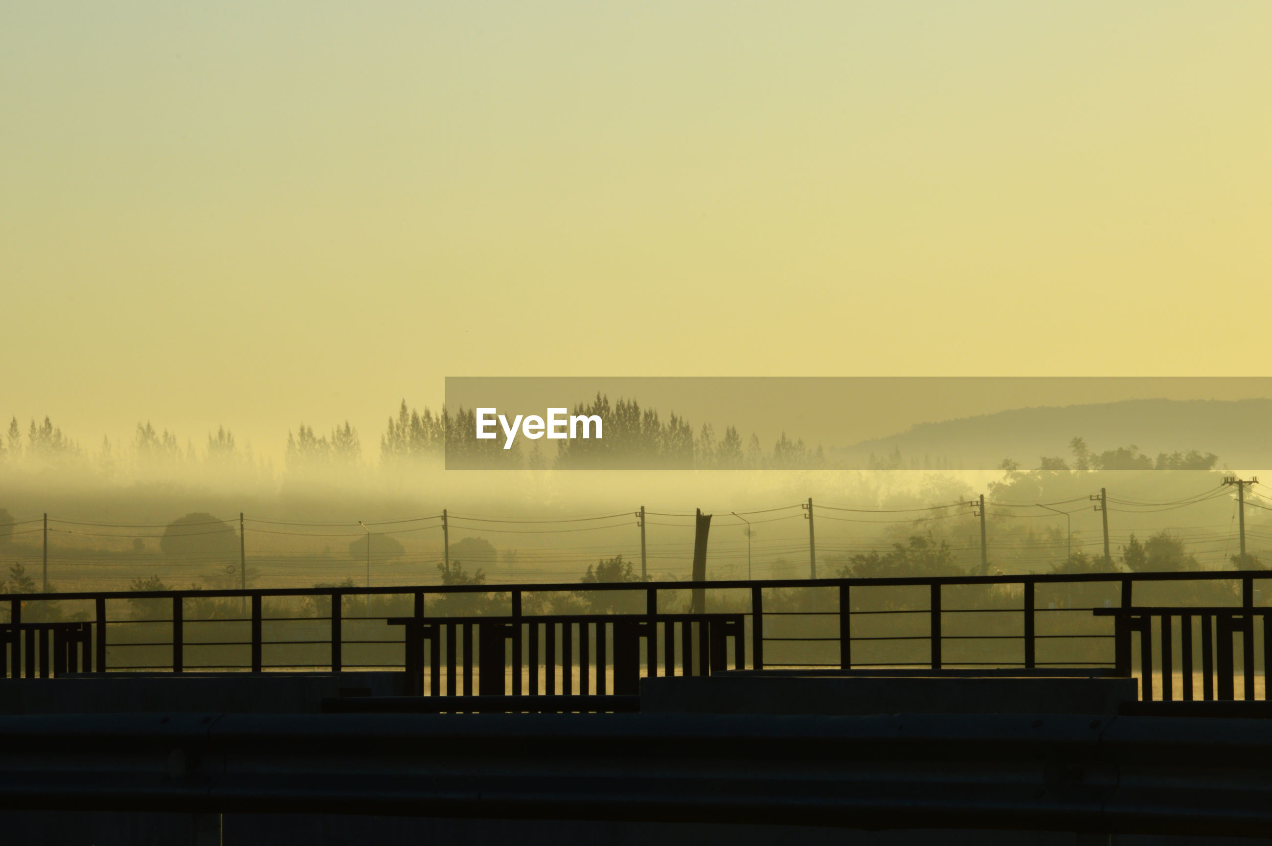 Scenic view of foggy weather against sky during sunset