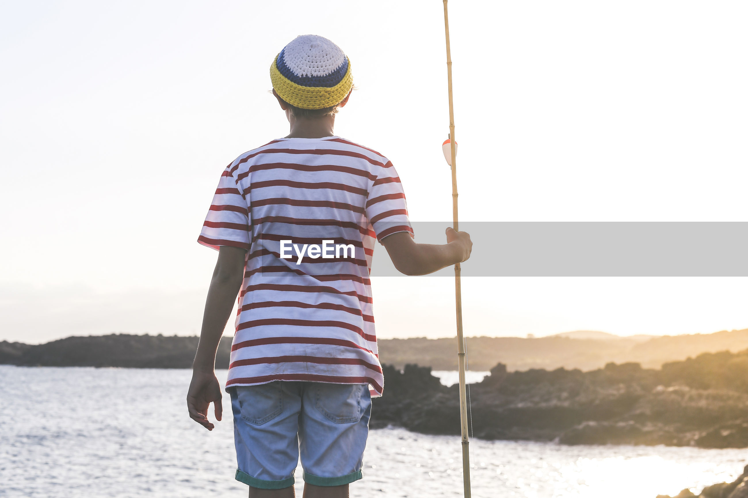 Rear view of boy holding fishing rod while standing against sky