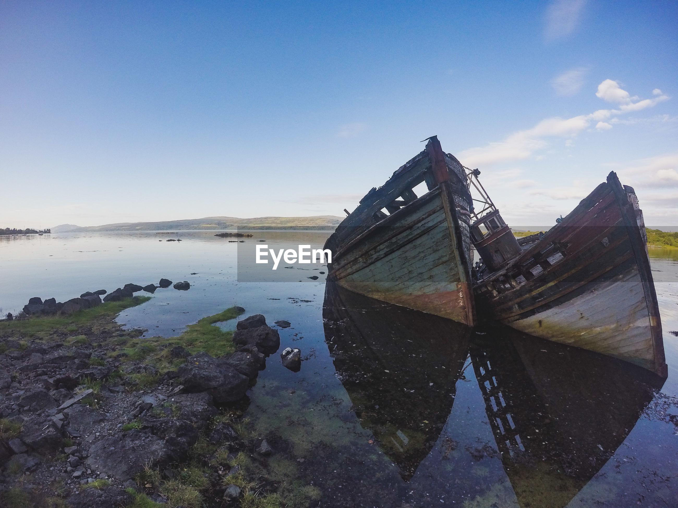 Boat wreck on beach against sky