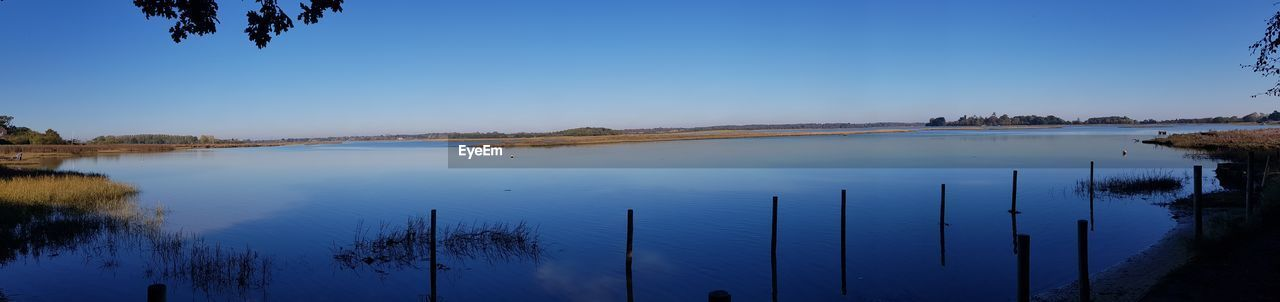 water, sky, tranquility, scenics - nature, beauty in nature, tranquil scene, blue, nature, plant, lake, tree, non-urban scene, reflection, clear sky, no people, panoramic, idyllic, outdoors, day