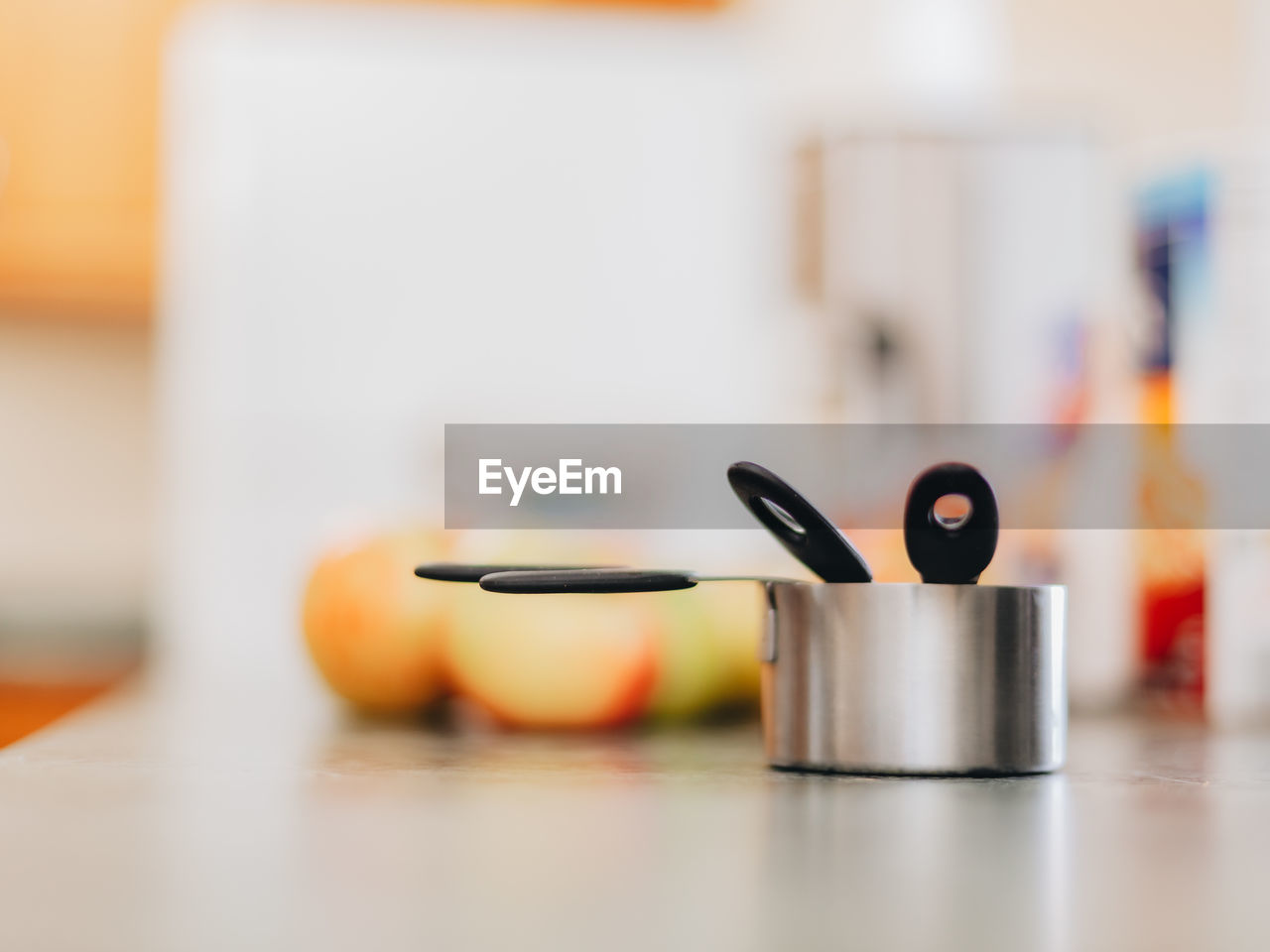 Apples and measuring cups on kitchen counter