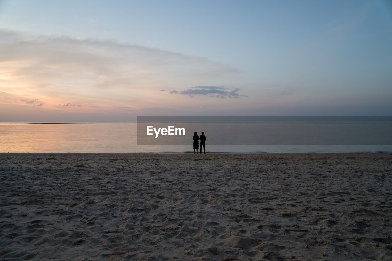 sky, sea, horizon, horizon over water, water, sunset, two people, beauty in nature, land, beach, scenics - nature, silhouette, cloud - sky, real people, togetherness, tranquility, men, standing, nature, couple - relationship, positive emotion, outdoors