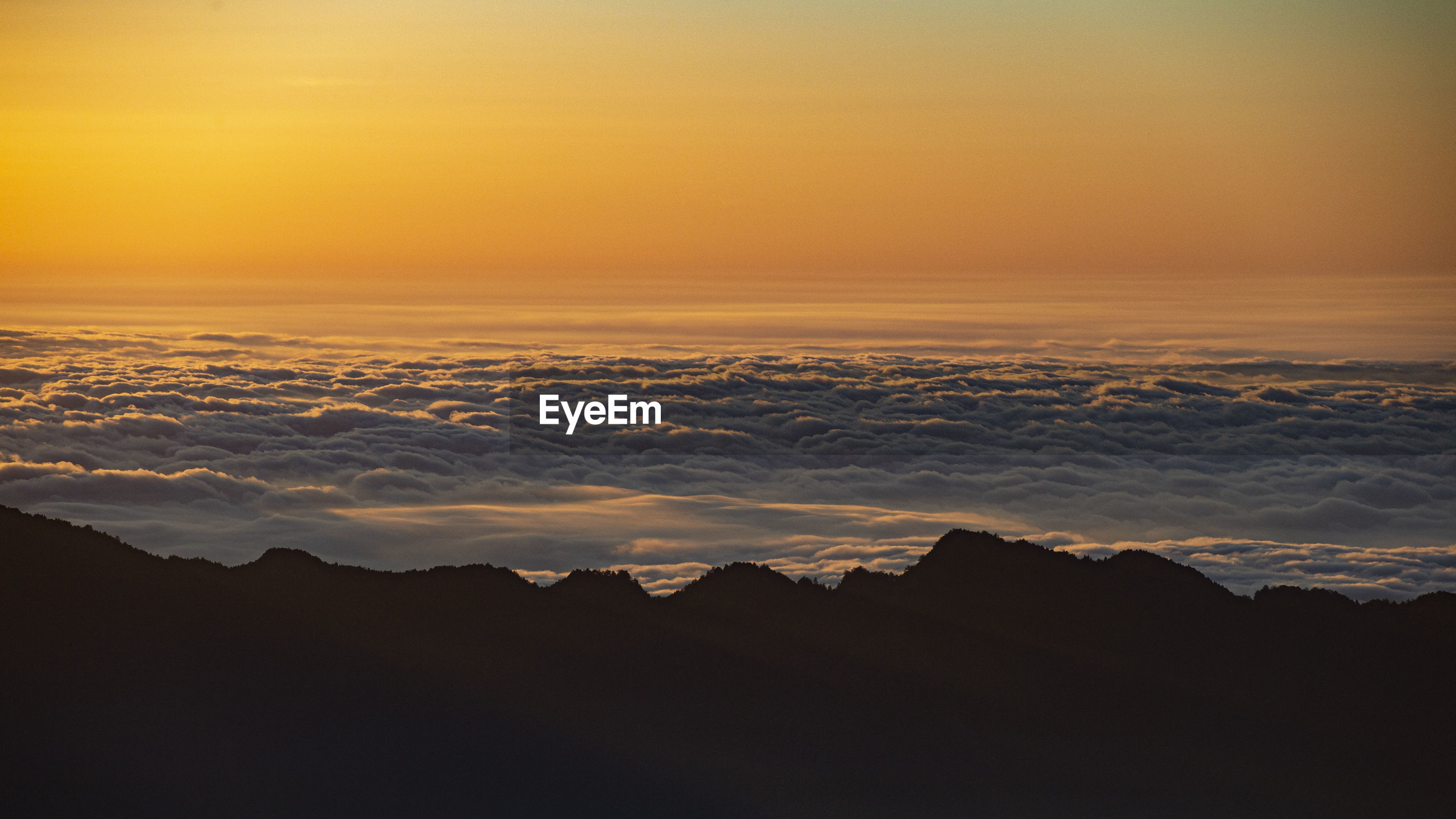 Scenic view of silhouette mountains against orange sky