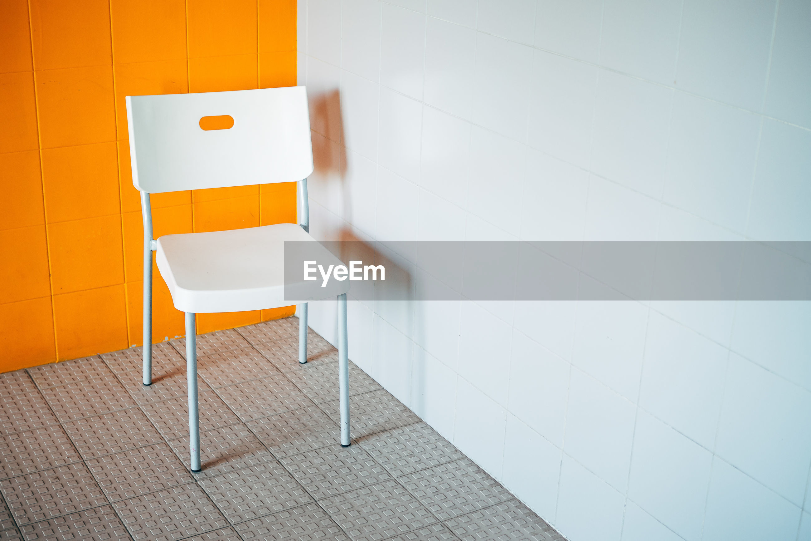 Empty white chair by wall at home