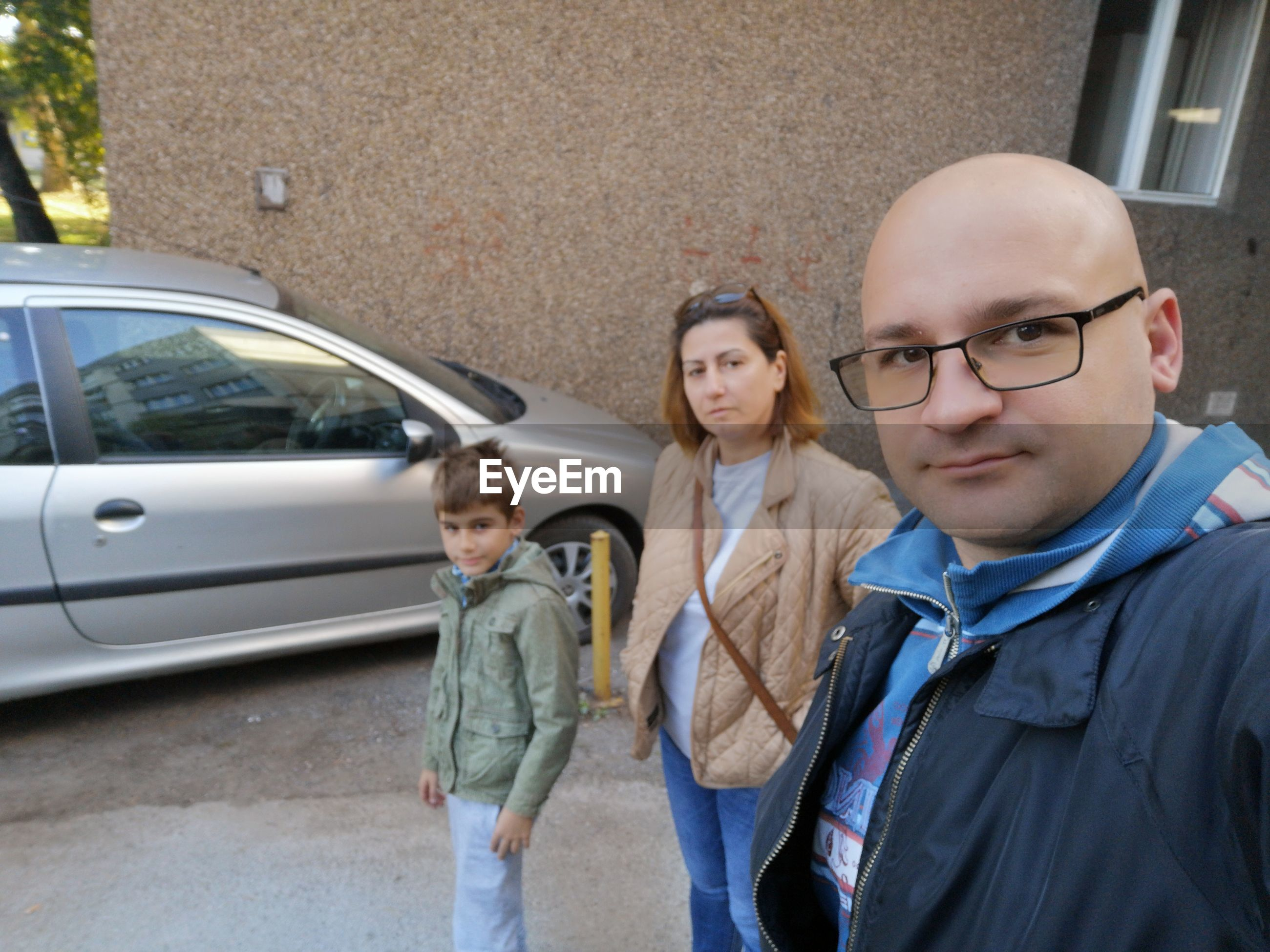 Portrait of family standing on road against building