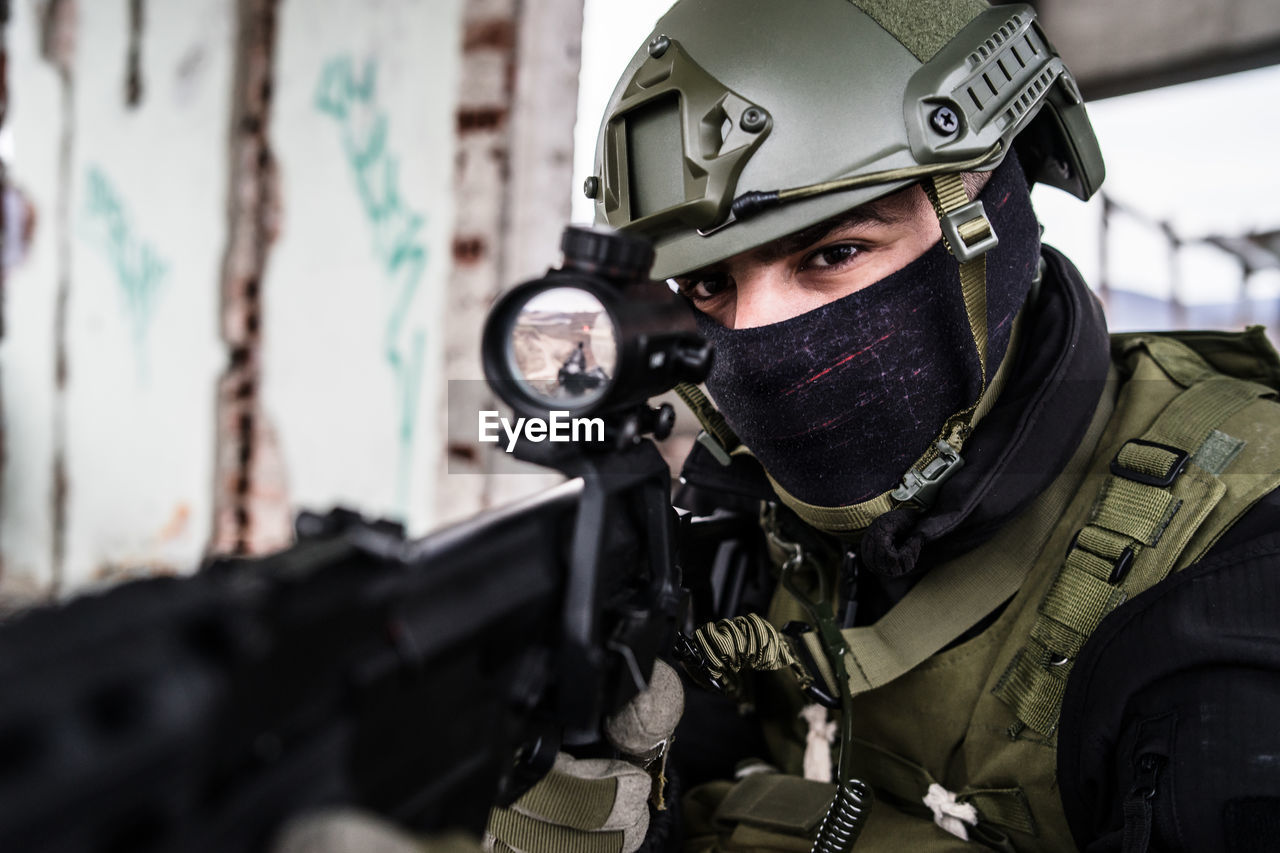 government, military, weapon, gun, clothing, uniform, men, armed forces, military uniform, protection, portrait, security, machine gun, one person, war, looking at camera, front view, protective workwear, police force, aggression, special forces