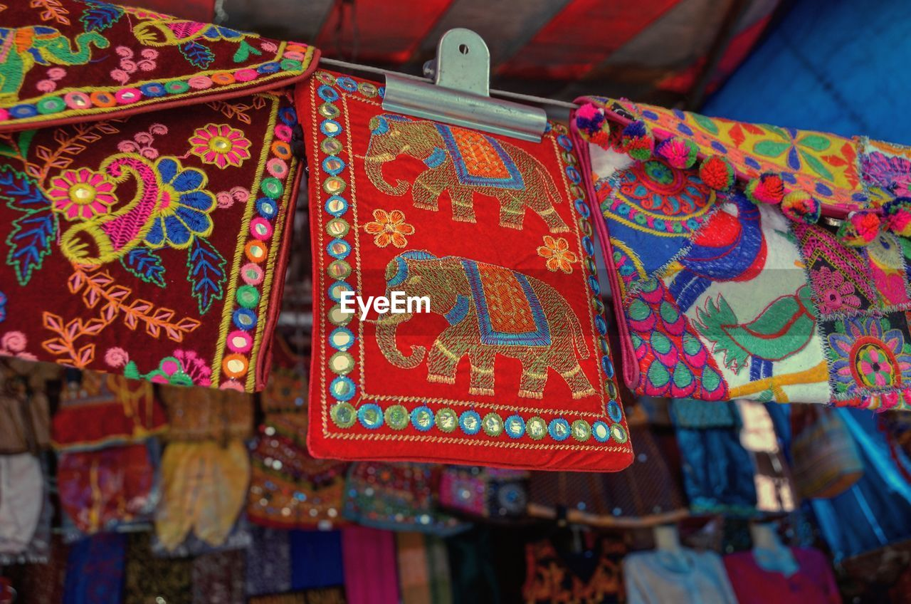 hanging, multi colored, market, for sale, focus on foreground, close-up, no people, retail, pattern, art and craft, communication, day, text, textile, red, craft, market stall, script, non-western script, creativity, retail display, sale, floral pattern