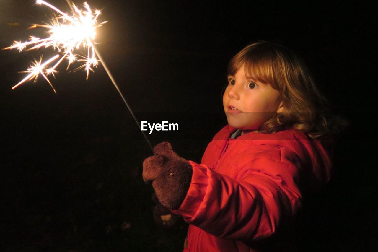 Scared Girl Holding Sparkler At Night