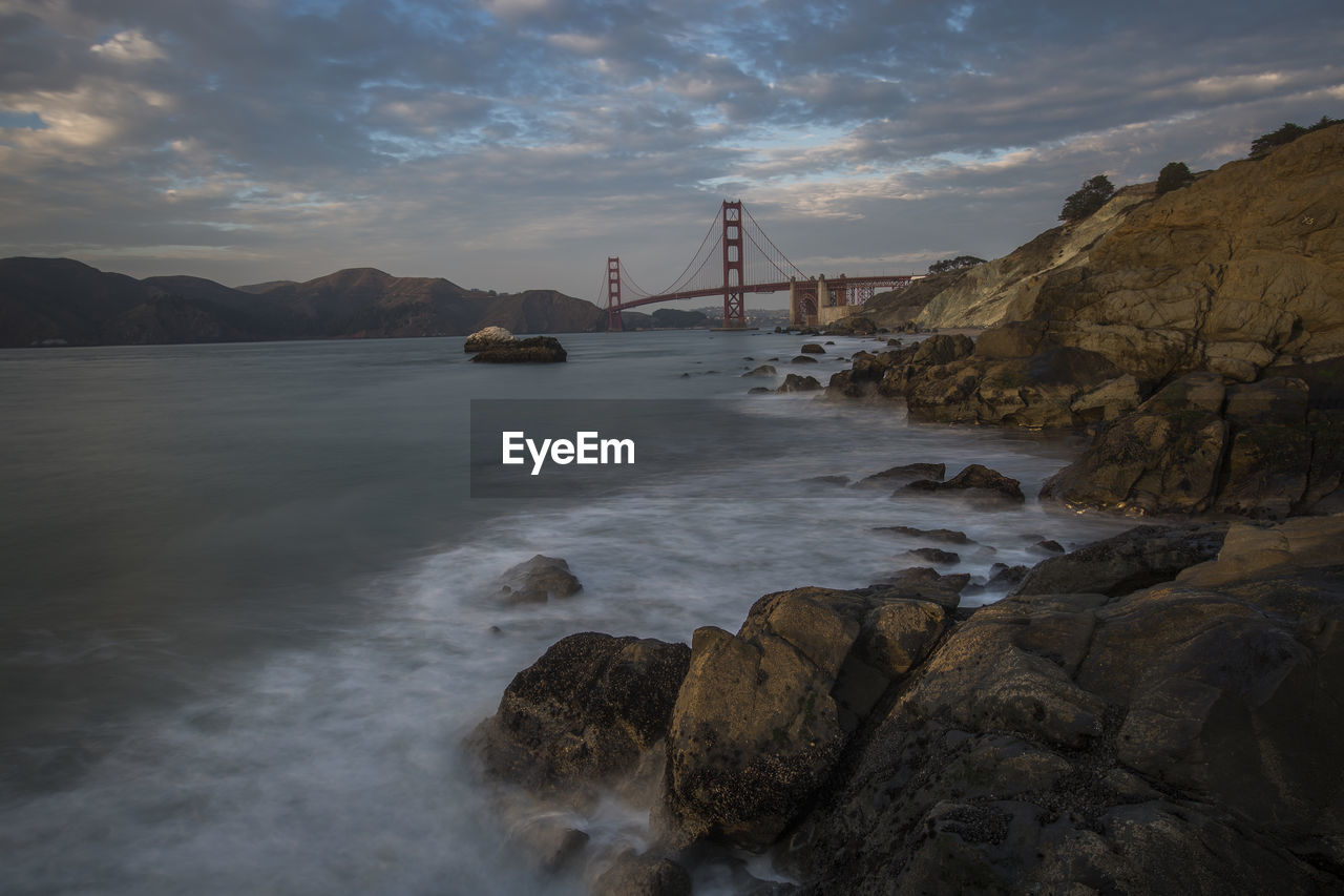 water, cloud - sky, sky, bridge, rock, connection, bridge - man made structure, beauty in nature, motion, sea, scenics - nature, solid, nature, built structure, rock - object, no people, transportation, architecture, mountain, bay, outdoors, flowing water