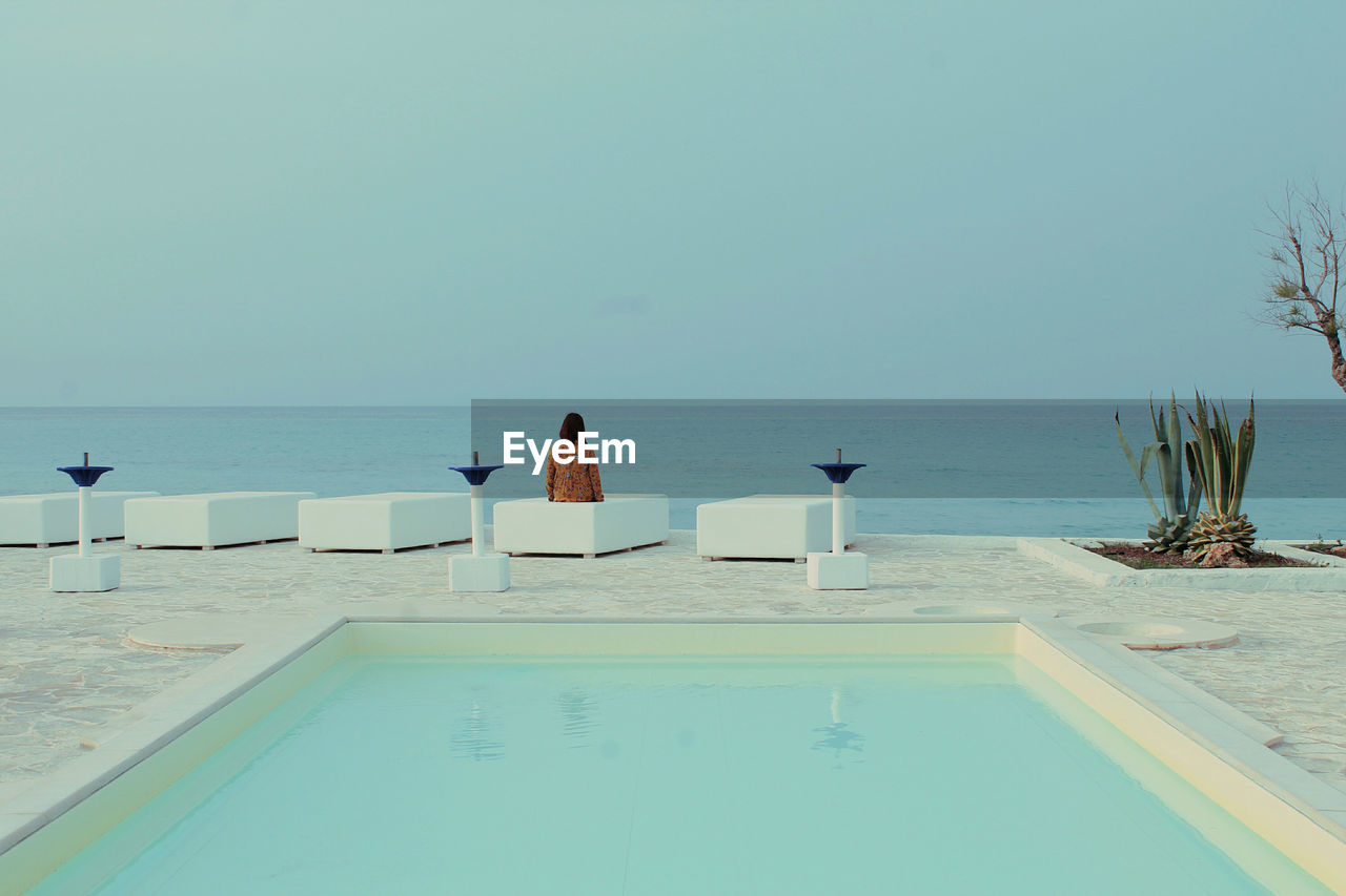 Rear view of woman sitting at poolside by sea against clear sky
