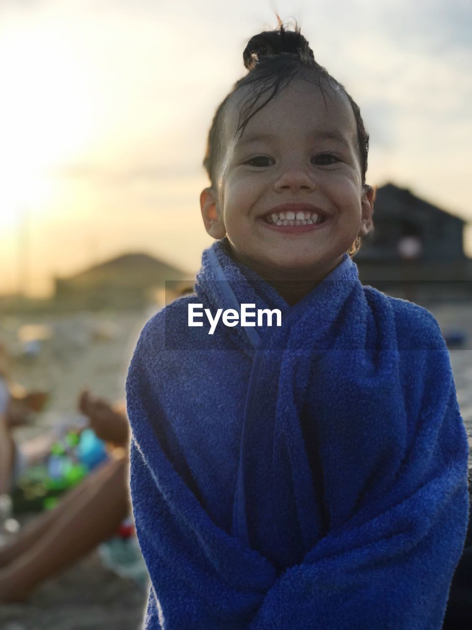 smiling, portrait, looking at camera, one person, focus on foreground, childhood, child, happiness, real people, men, boys, front view, sky, males, leisure activity, waist up, lifestyles, emotion, nature, outdoors, innocence