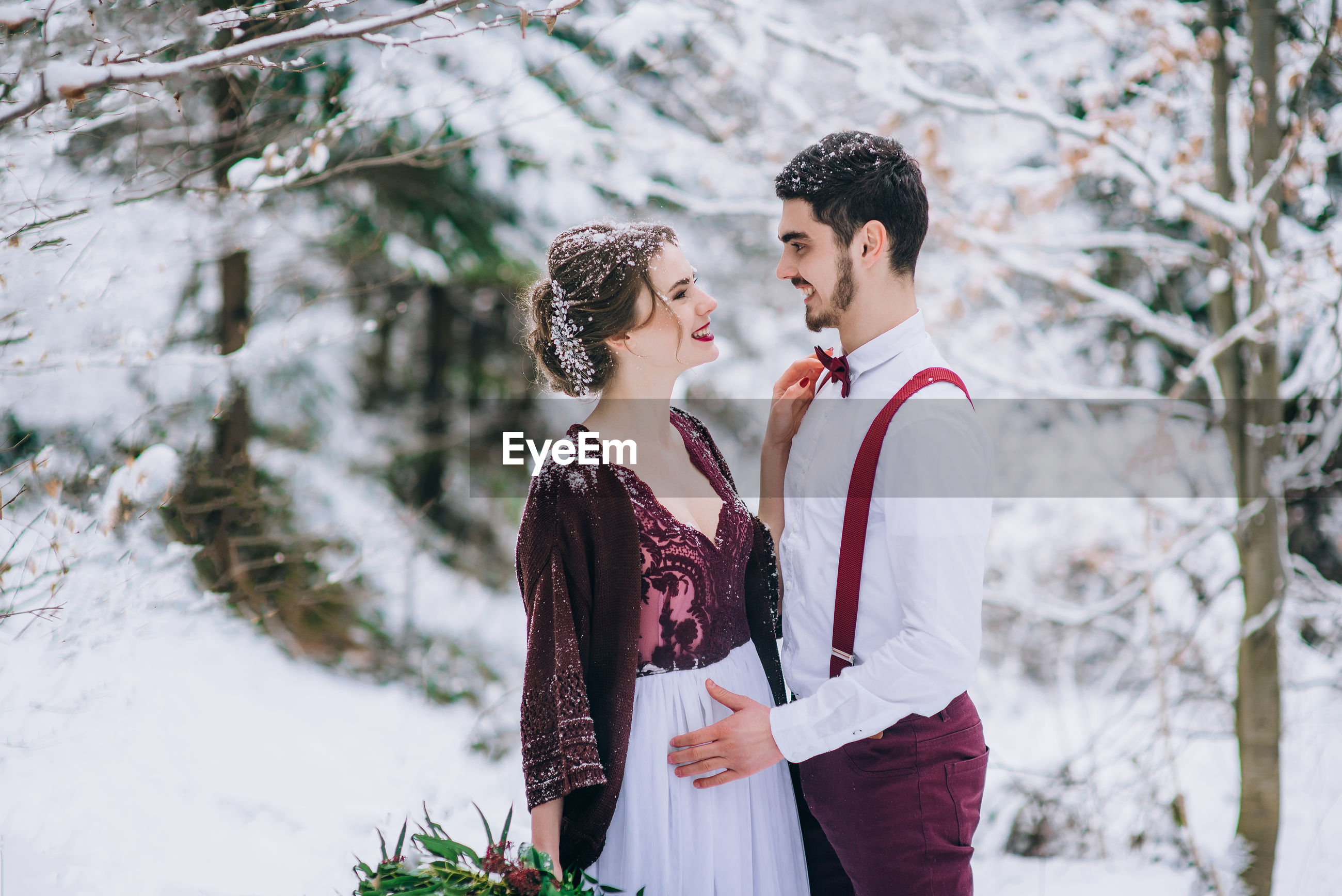 YOUNG COUPLE STANDING IN SNOW
