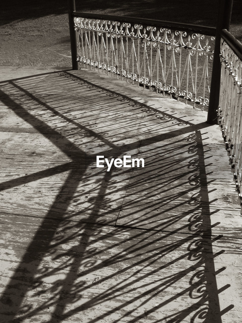 shadow, sunlight, architecture, no people, built structure, railing, wood - material, footpath, nature, pattern, day, high angle view, outdoors, absence, the way forward, metal, direction, flooring, bridge, wood, focus on shadow, paving stone