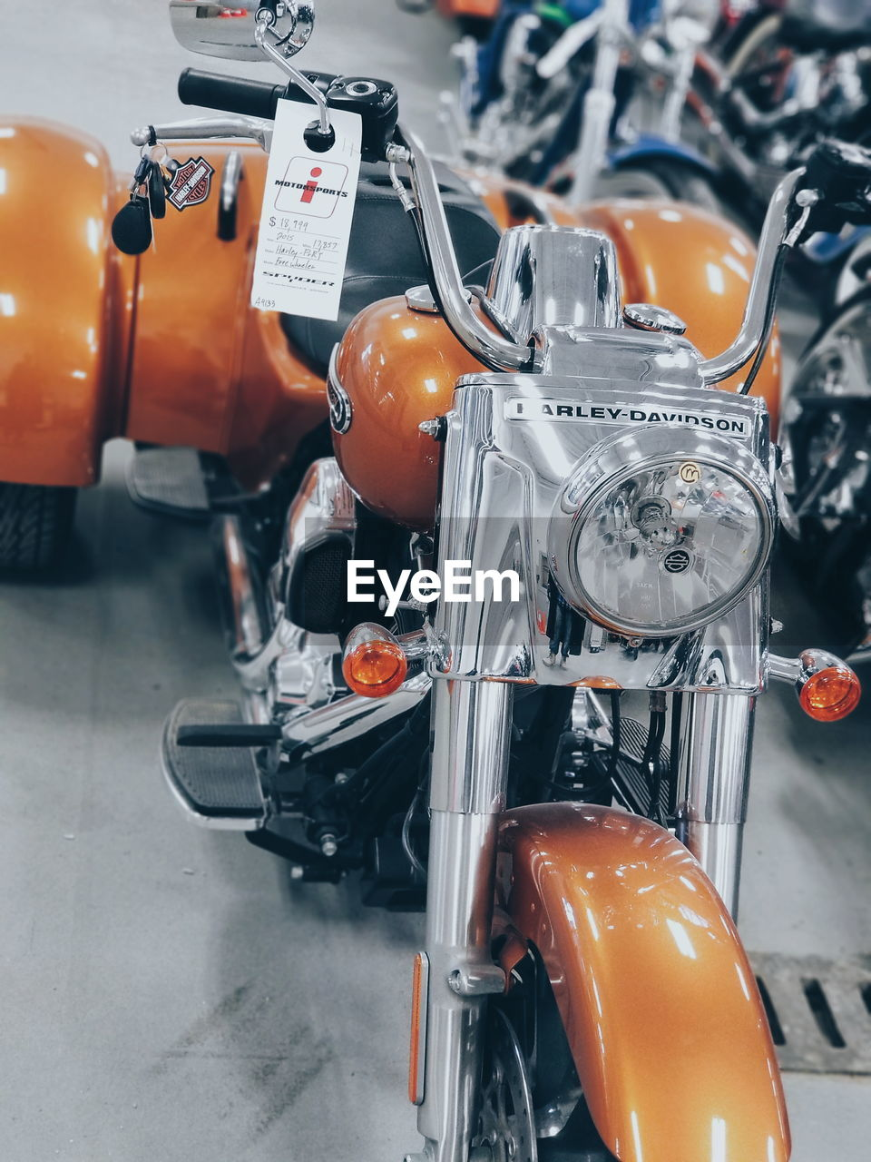 mode of transportation, transportation, land vehicle, stationary, orange color, motorcycle, headlight, no people, scooter, city, bicycle, still life, motor scooter, street, motor vehicle, focus on foreground, day, car, outdoors, road, wheel