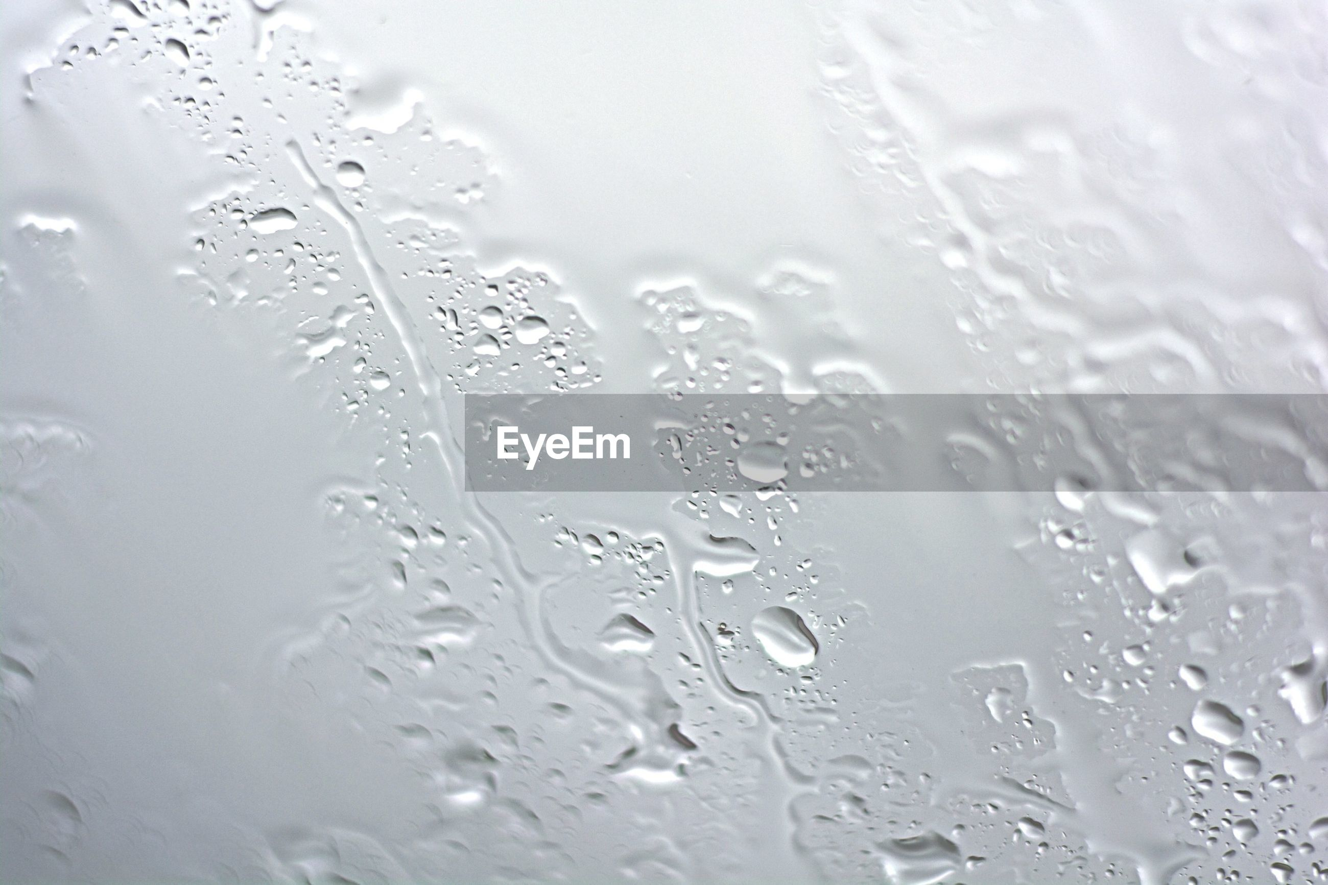 EXTREME CLOSE UP OF WATER DROPS ON WOODEN SURFACE