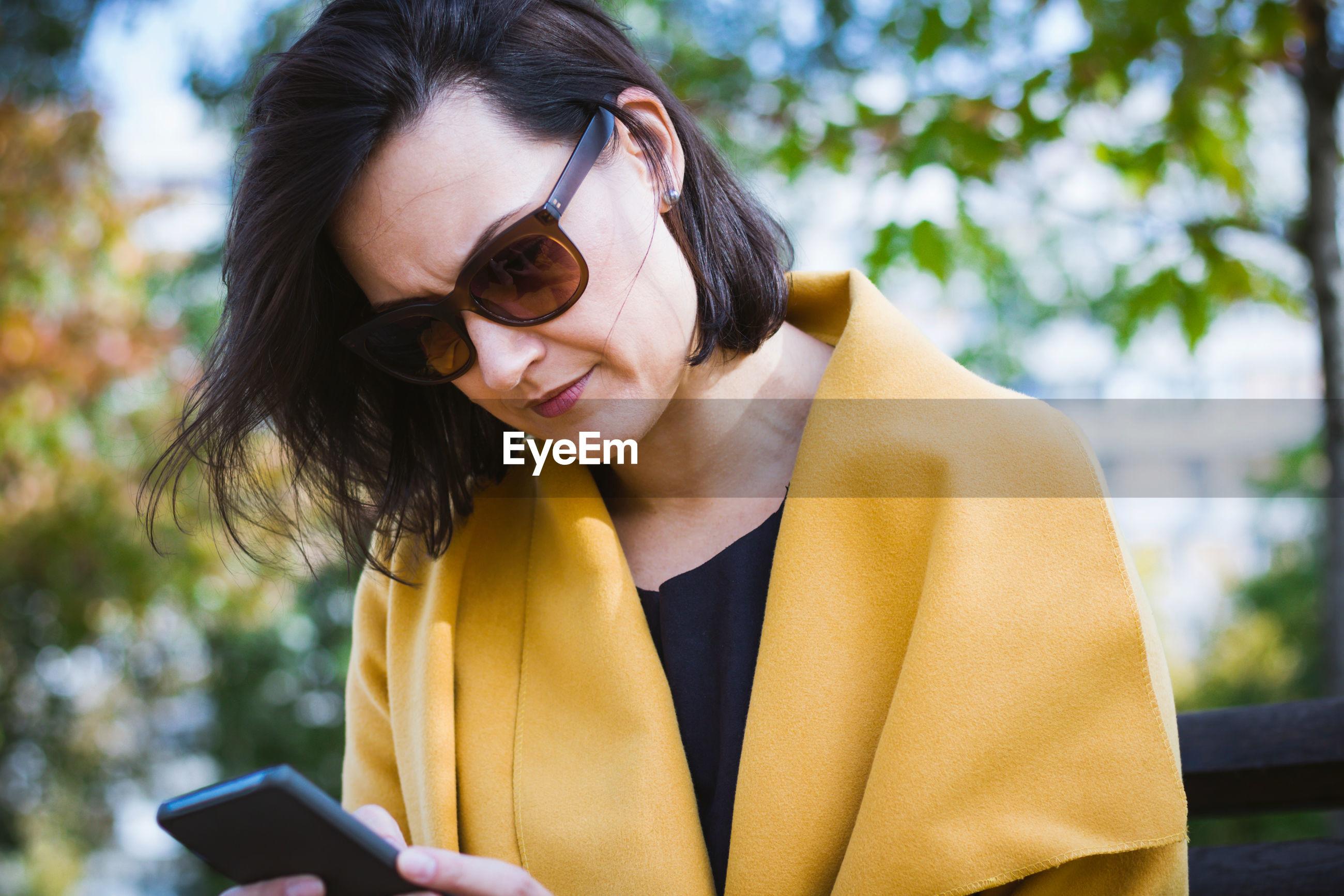 Beautiful woman using smart phone at public park