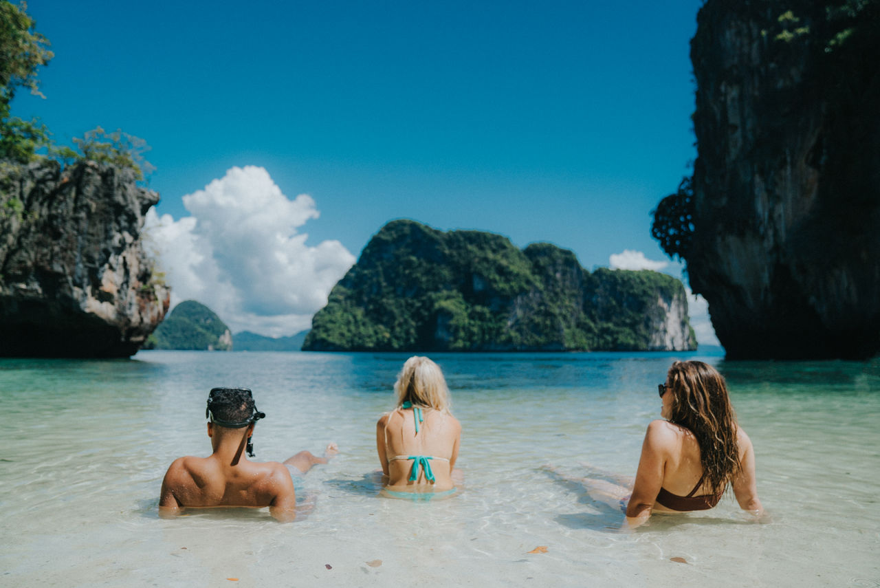 Rear View Of Friends Relaxing At Beach