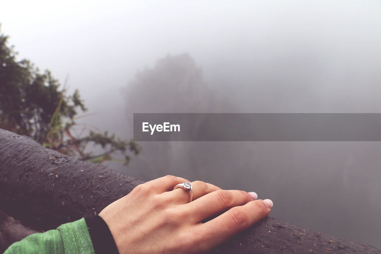 Cropped hand of woman on railing during foggy weather