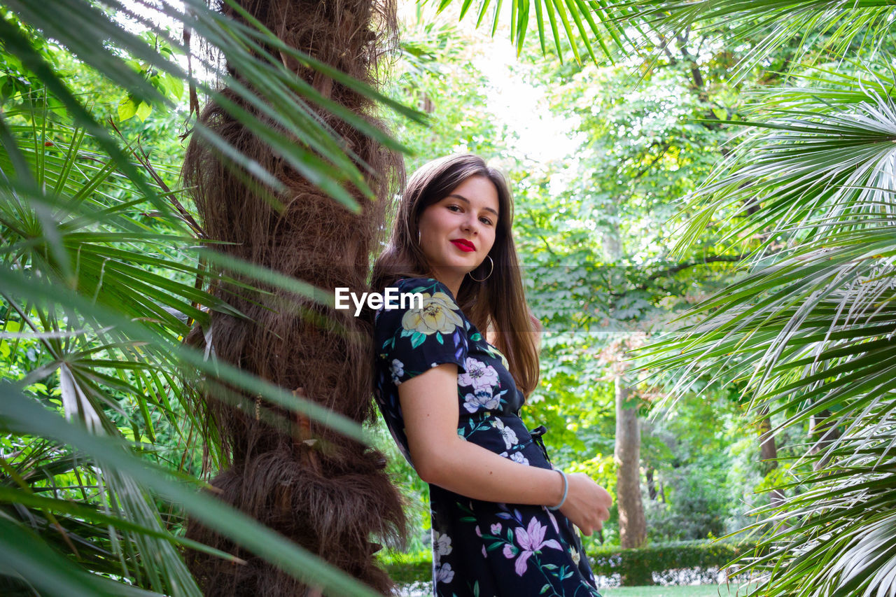 Portrait of smiling young woman by tree trunk