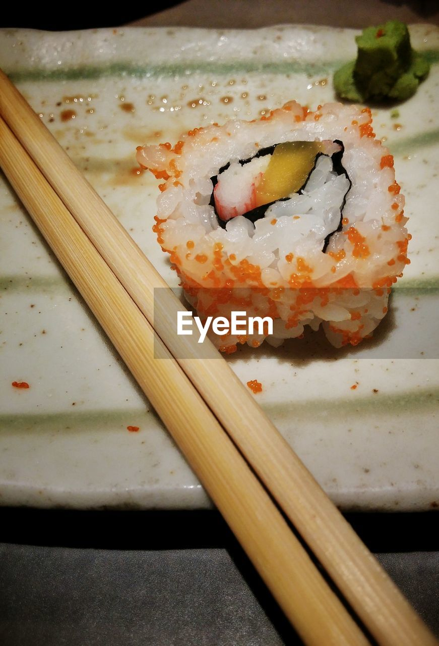 High Angle View Of California Roll And Chopsticks Served In Plate
