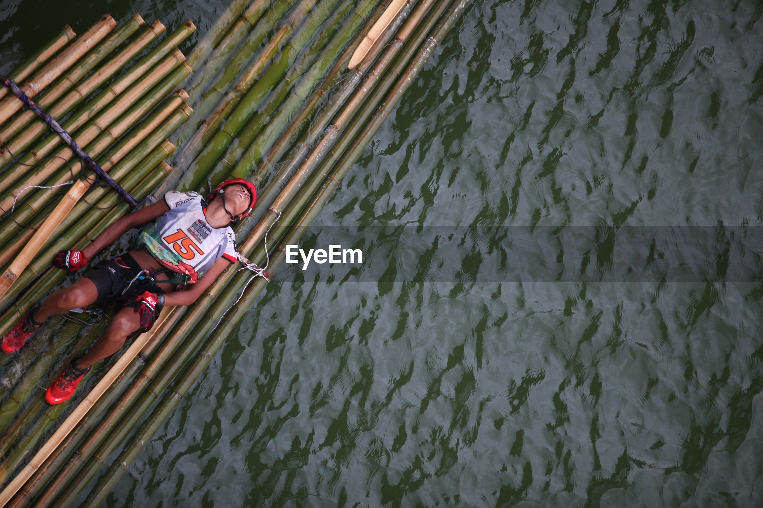 High angle view of man lying on wooden raft over river
