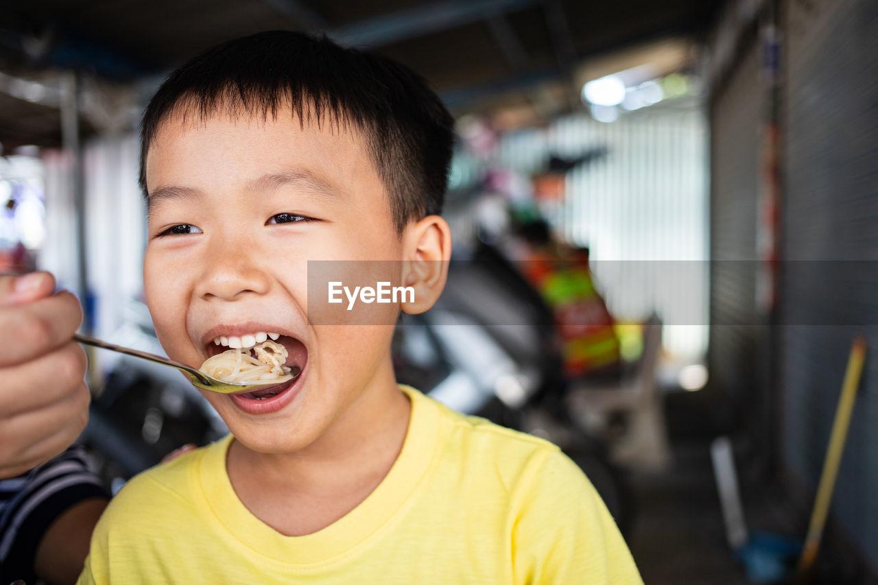 PORTRAIT OF BOY EATING