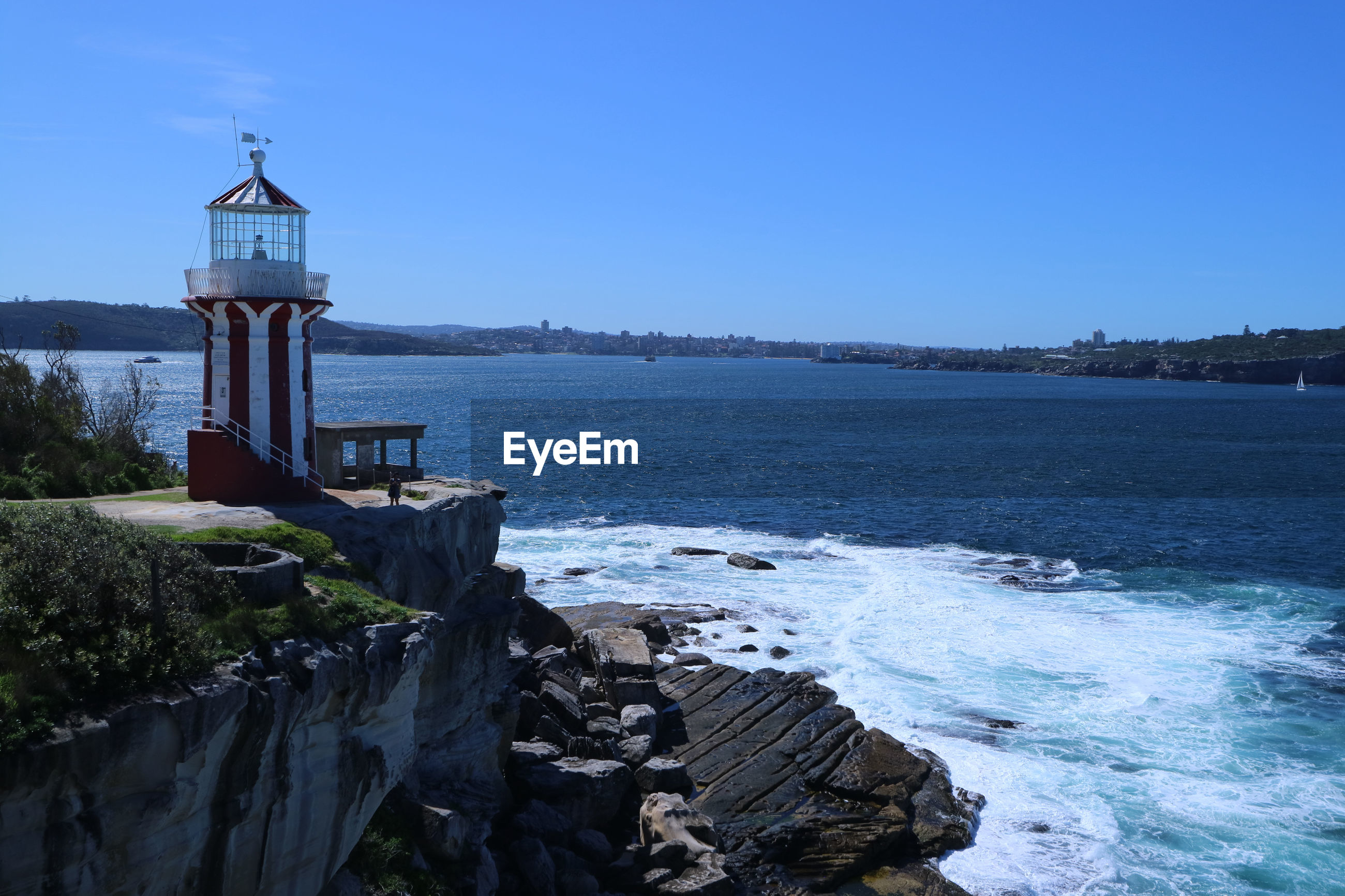 LIGHTHOUSE AMIDST SEA AGAINST CLEAR SKY