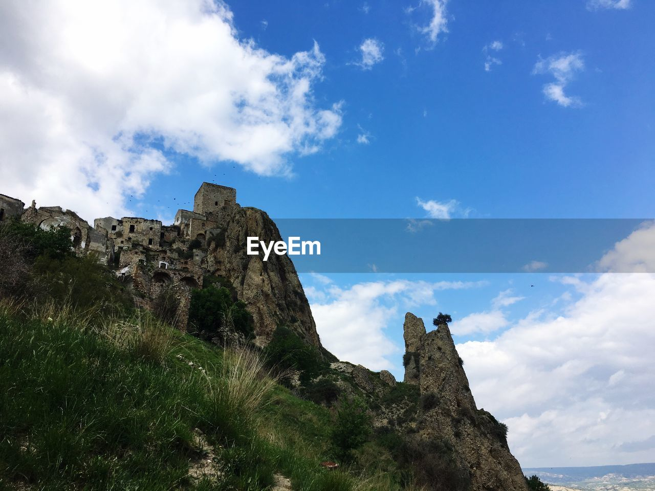 rock - object, rock formation, sky, cliff, nature, cloud - sky, scenics, day, mountain, low angle view, tranquility, travel destinations, history, outdoors, tranquil scene, beauty in nature, architecture, castle, built structure, building exterior, landscape, no people
