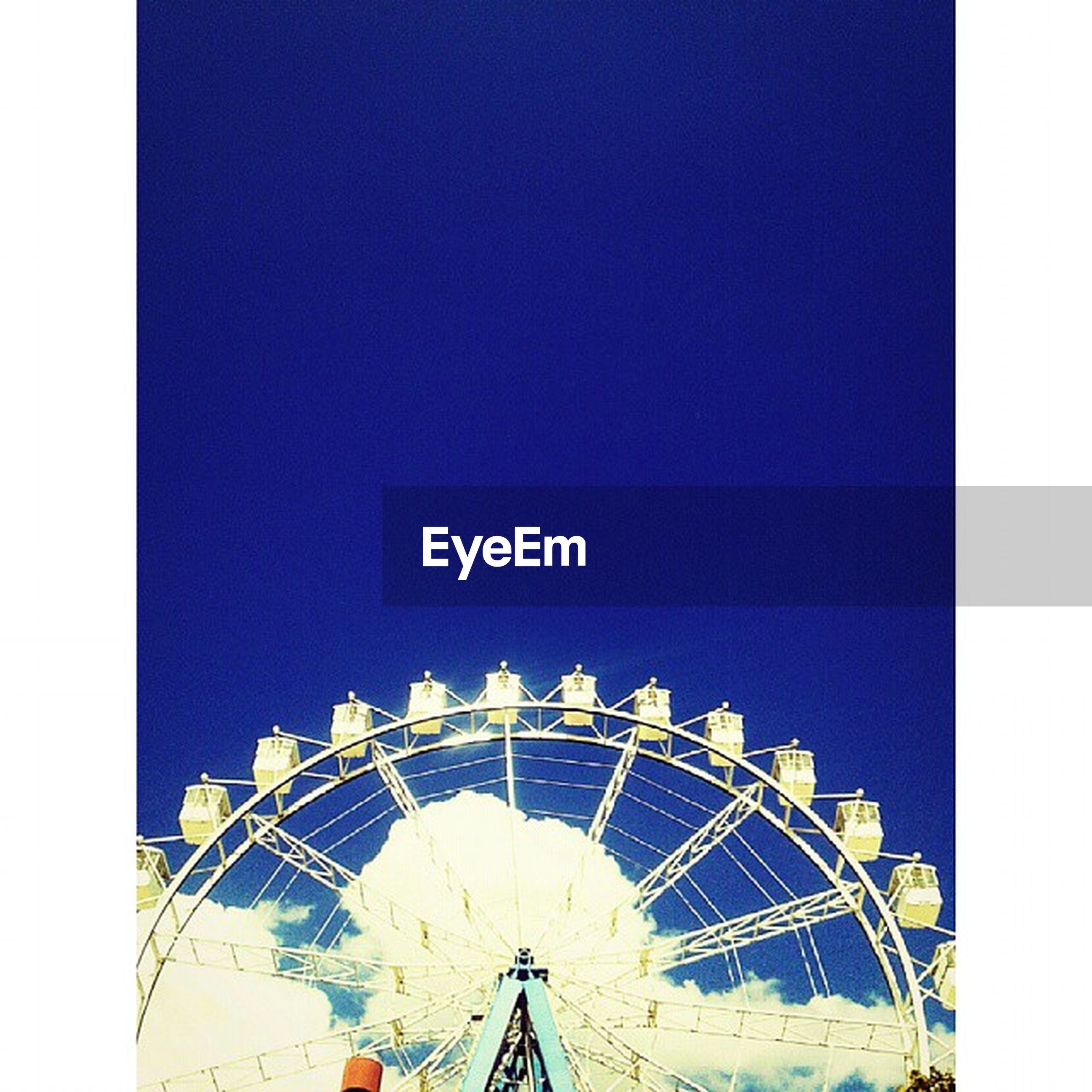 ferris wheel, low angle view, amusement park, amusement park ride, clear sky, arts culture and entertainment, copy space, sky, blue, outdoors, day, built structure, auto post production filter, no people, part of, high section, architecture, fun, metal, nature