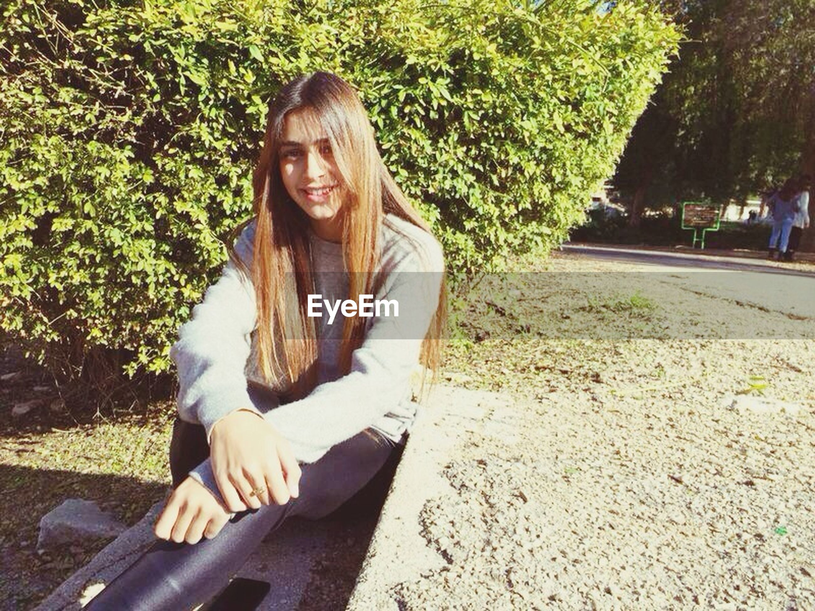 lifestyles, person, casual clothing, leisure activity, young adult, sitting, young women, portrait, looking at camera, smiling, tree, relaxation, front view, three quarter length, waist up, full length, sunlight, park - man made space