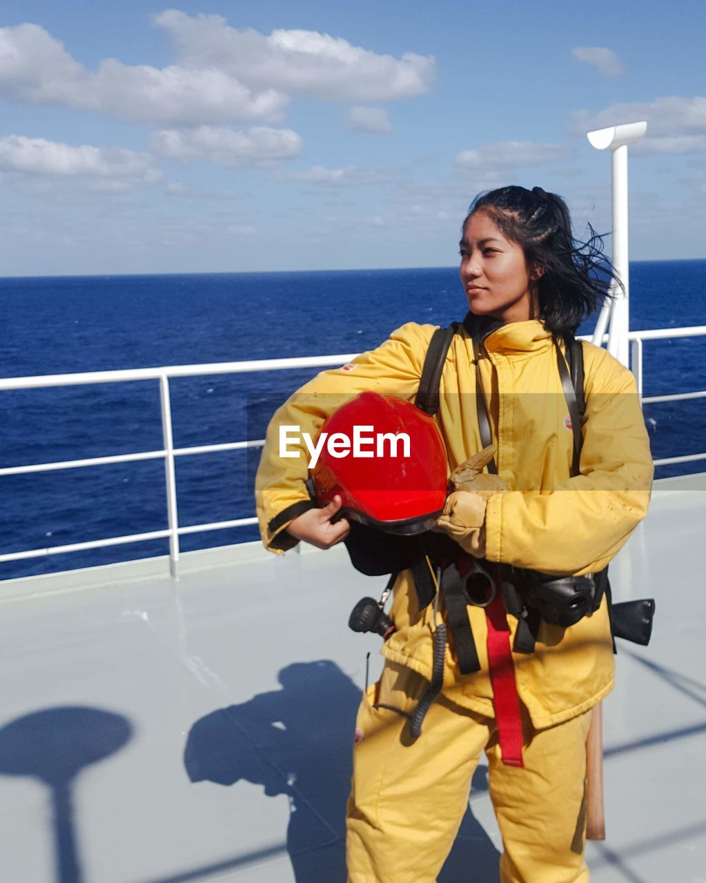 Woman in uniform standing on boat at sea against sky