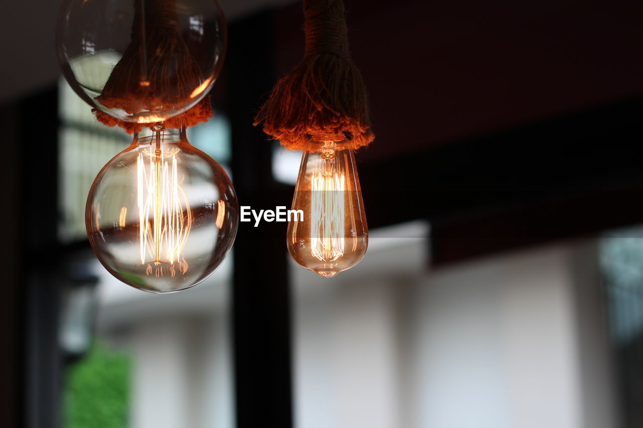 lighting equipment, focus on foreground, glass - material, hanging, light bulb, close-up, no people, illuminated, electricity, indoors, transparent, low angle view, electric light, light, decoration, day, filament, glowing, selective focus, technology, ceiling, electric lamp