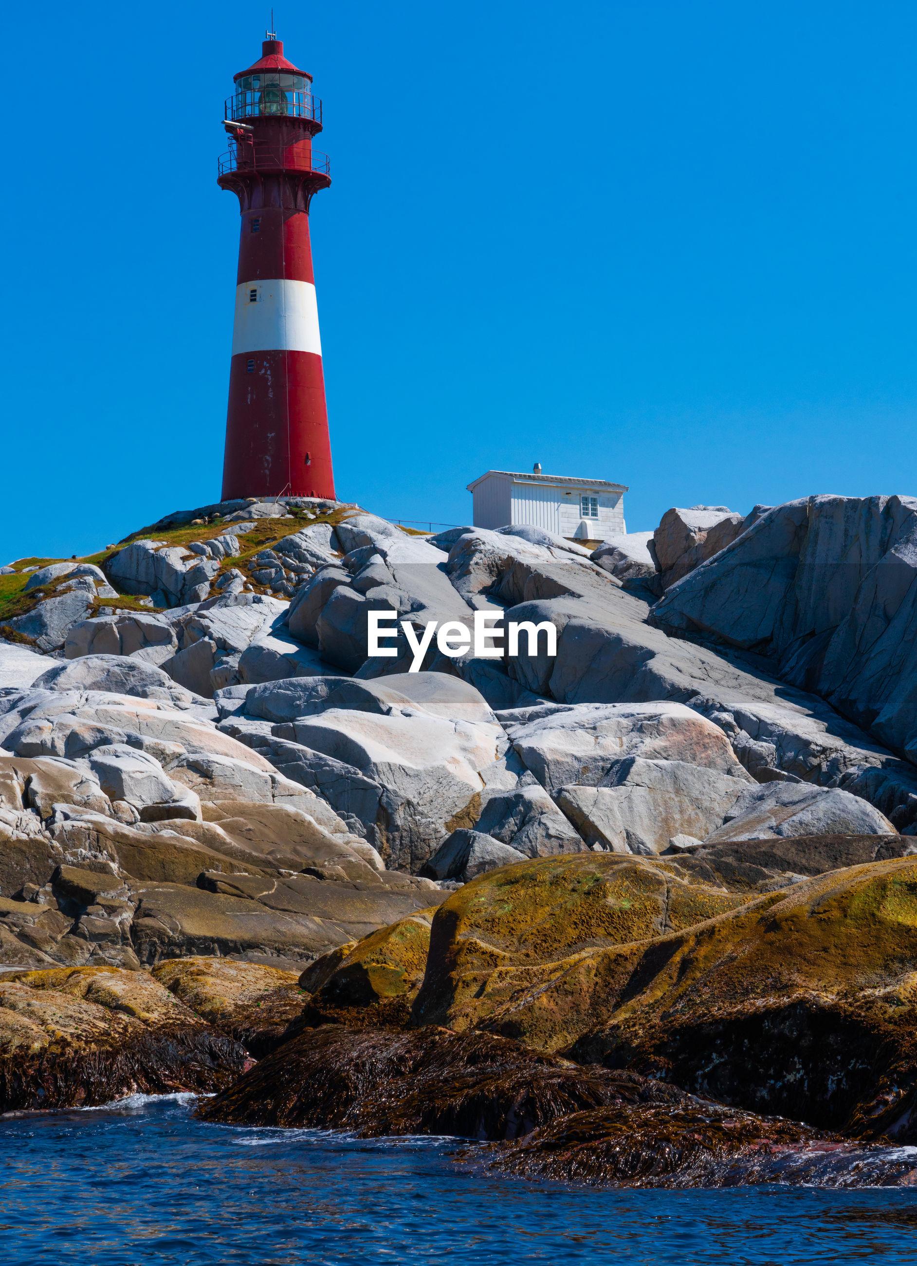 Lighthouse at beach against clear blue sky