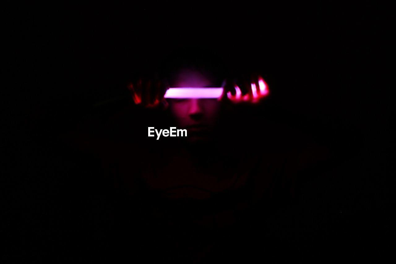 Close-Up Of Illuminated Person In Darkroom