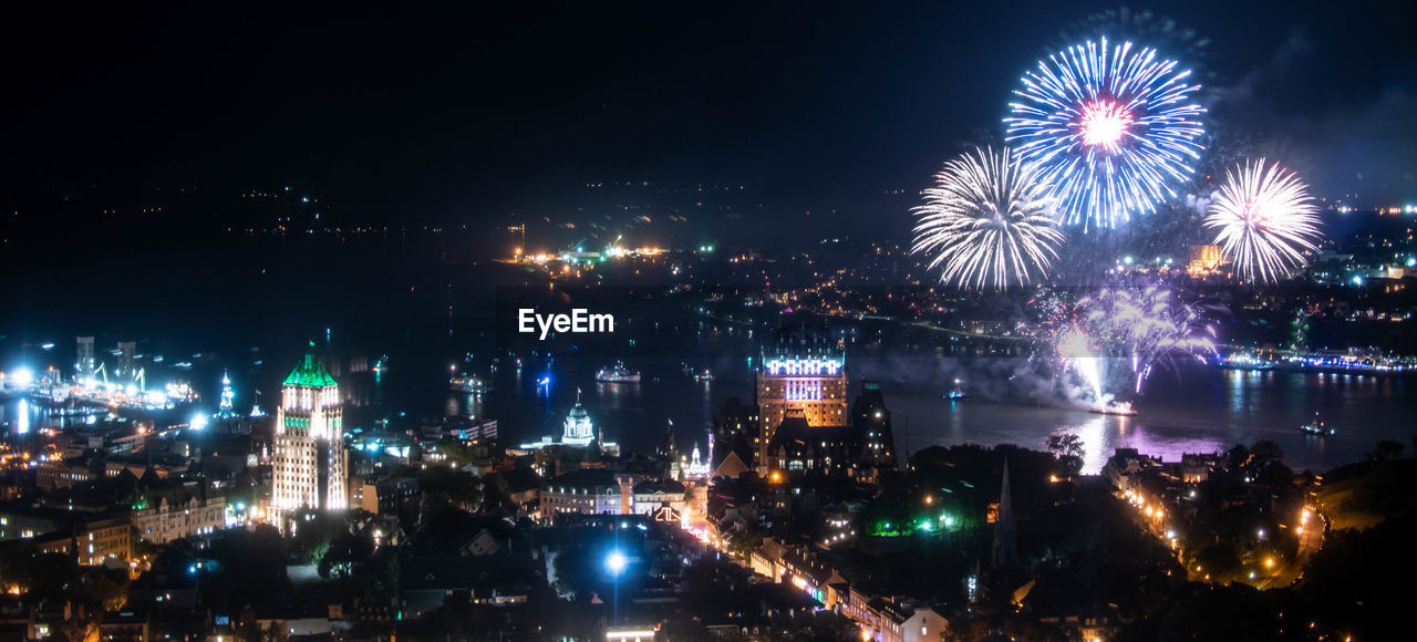 FIREWORK DISPLAY OVER ILLUMINATED BUILDINGS IN CITY