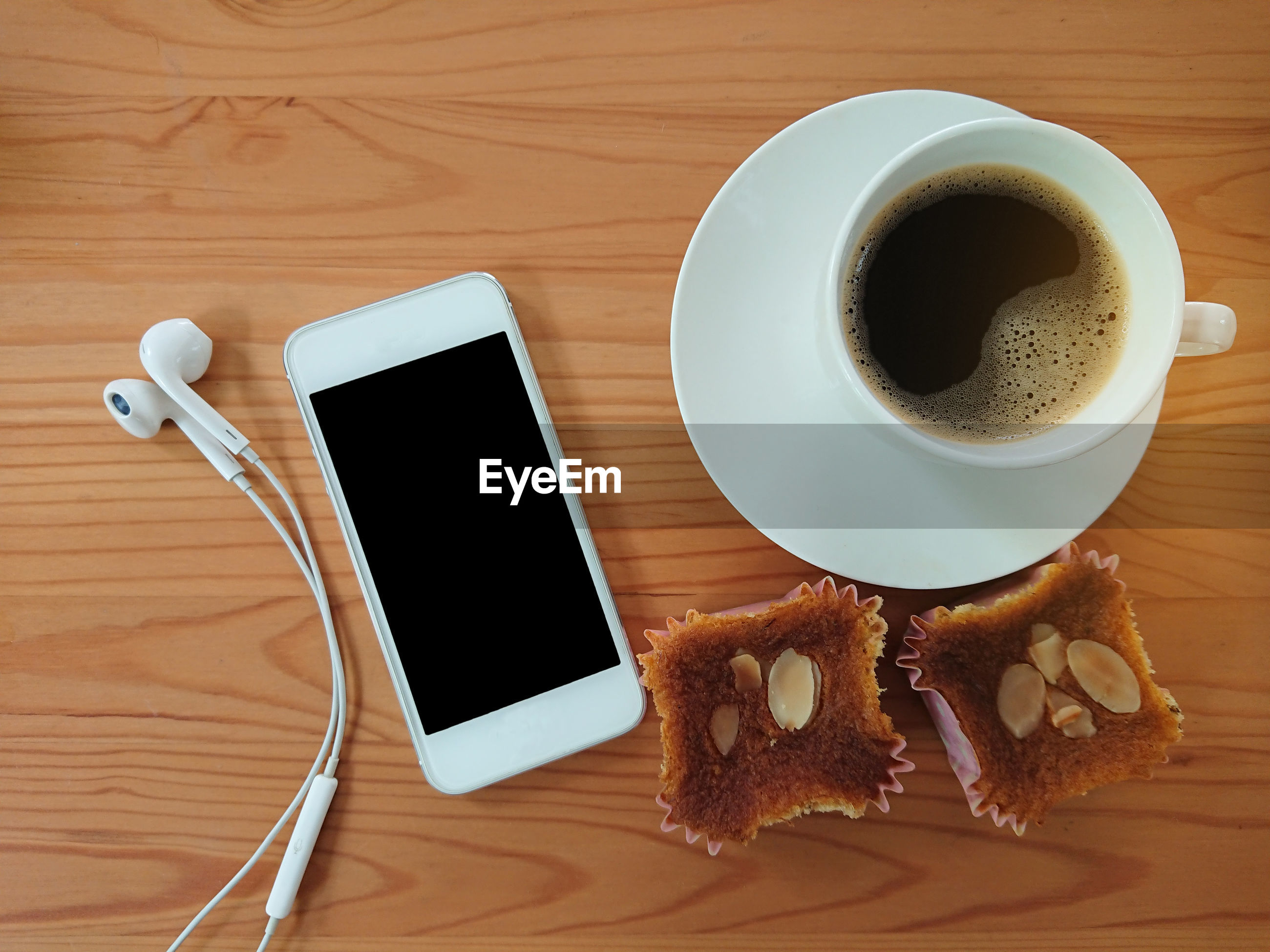 High angle view of food and drink by mobile phone on table