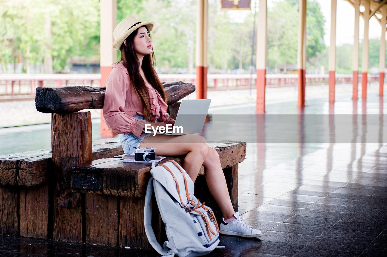 Woman using laptop while sitting at railroad station platform
