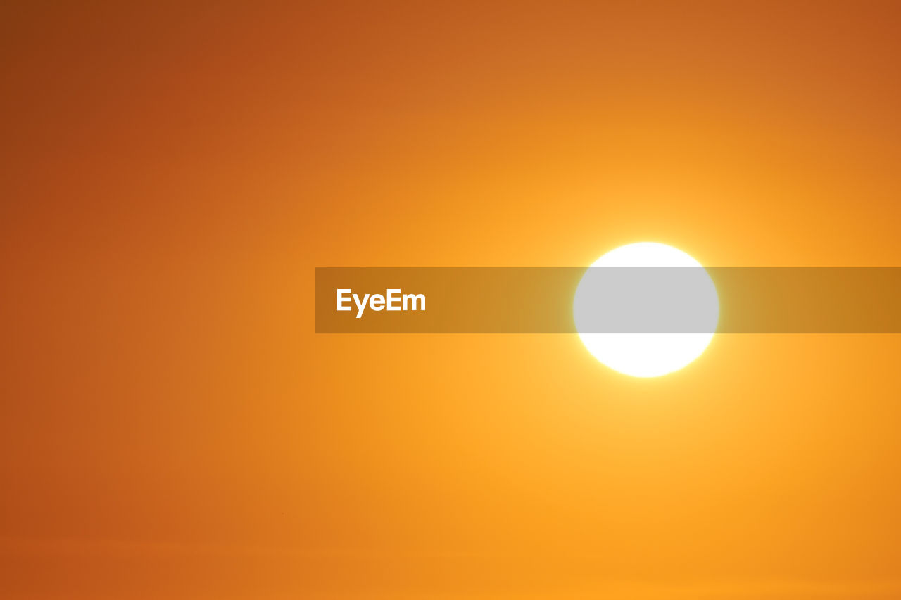 orange color, sky, beauty in nature, sunset, scenics - nature, sun, tranquil scene, tranquility, circle, yellow, geometric shape, no people, sunlight, outdoors, nature, solar eclipse, shape, idyllic, astronomy, eclipse, bright, brightly lit