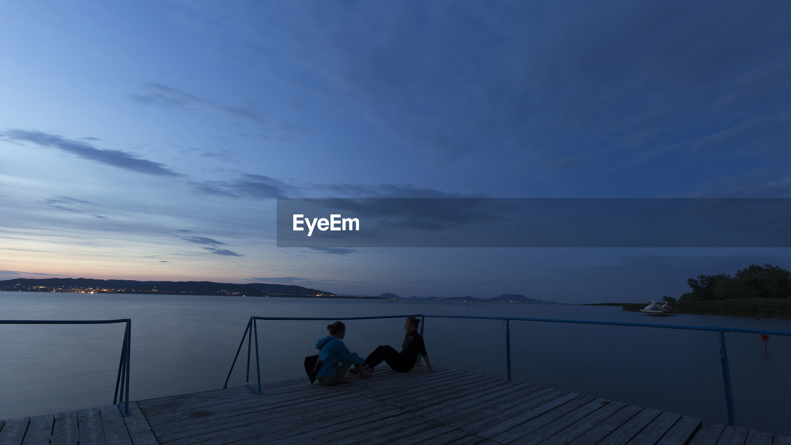Couple sitting on pier over sea against sky