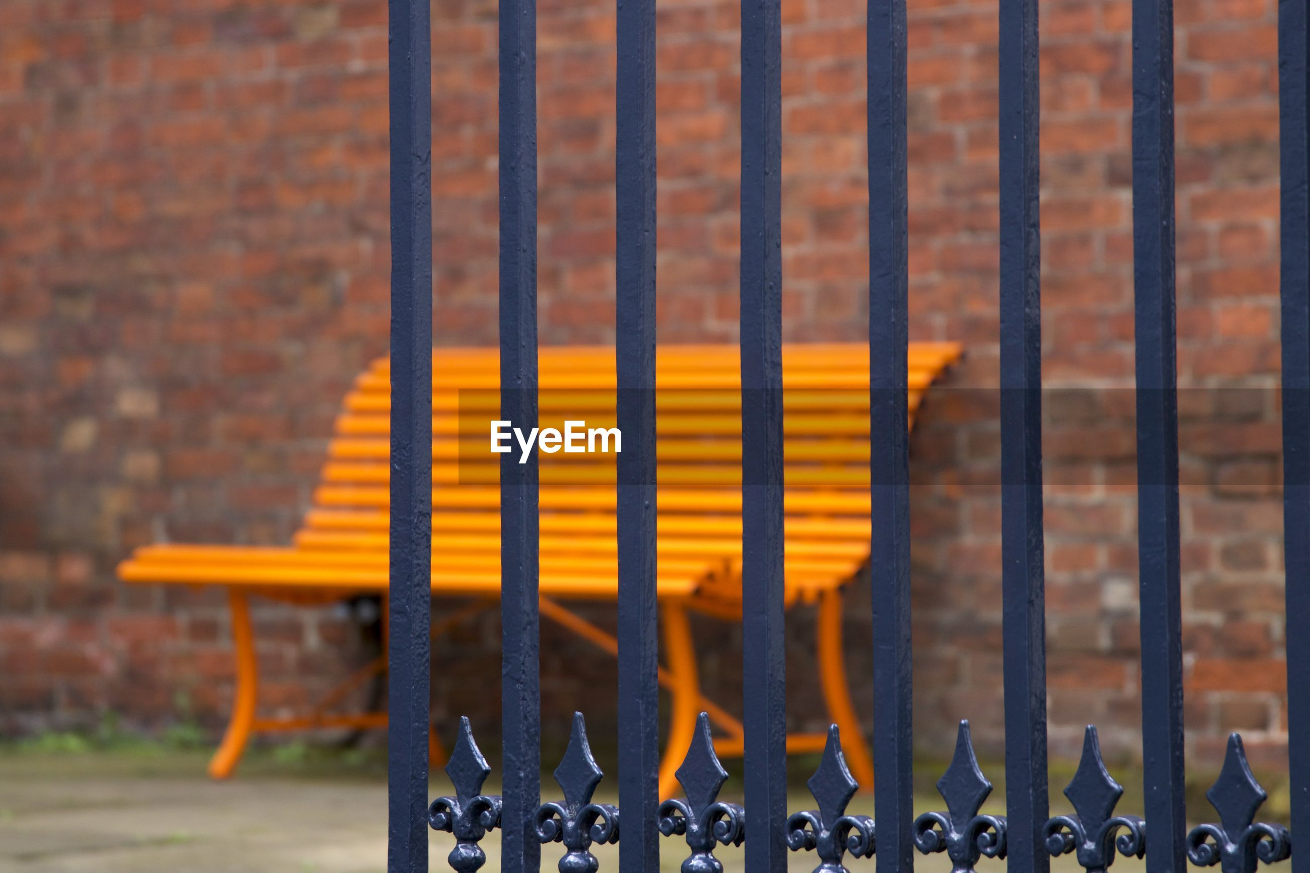 Close-Up Of Empty Bench Seen Through Gate
