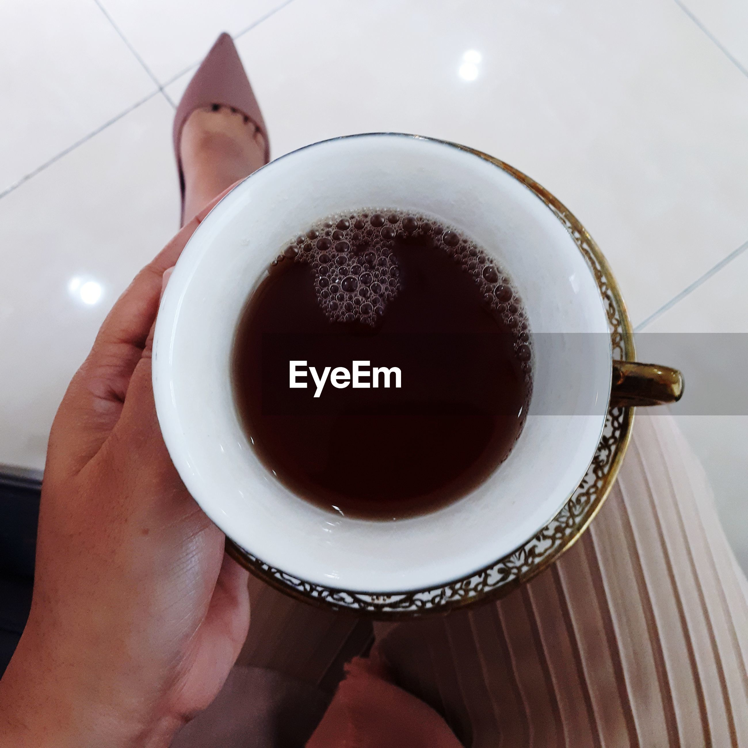 HIGH ANGLE VIEW OF HAND HOLDING COFFEE CUP OF TEA