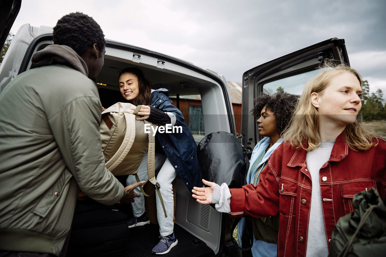 HAPPY FRIENDS STANDING ON CAR AGAINST PEOPLE