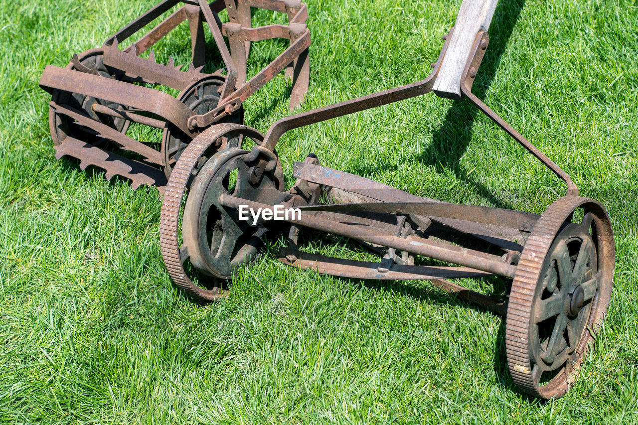 Pair of old fashioned push lawn mowers on a green lawn