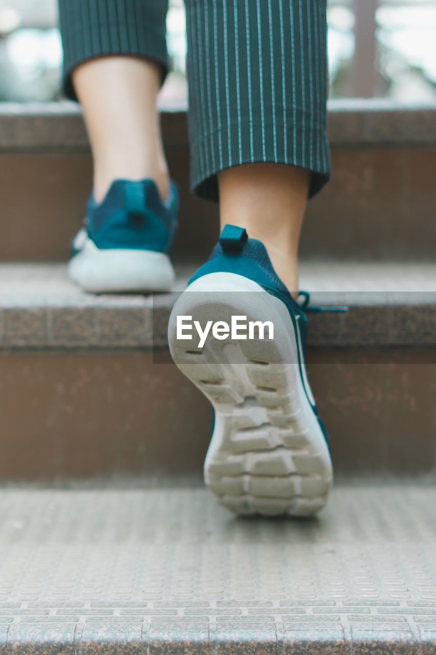 Low section of person walking on steps