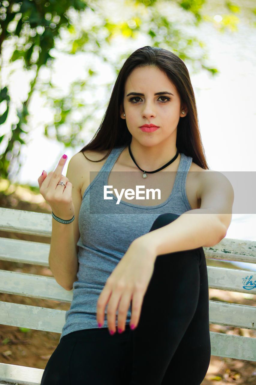 Portrait of young woman showing obscene gesture while sitting on bench