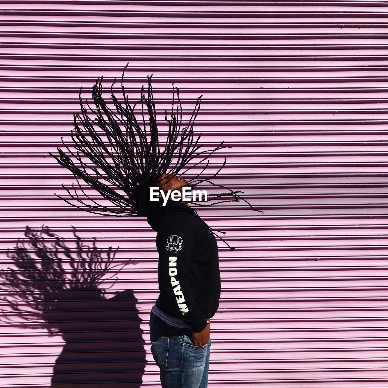 MAN STANDING ON UMBRELLA