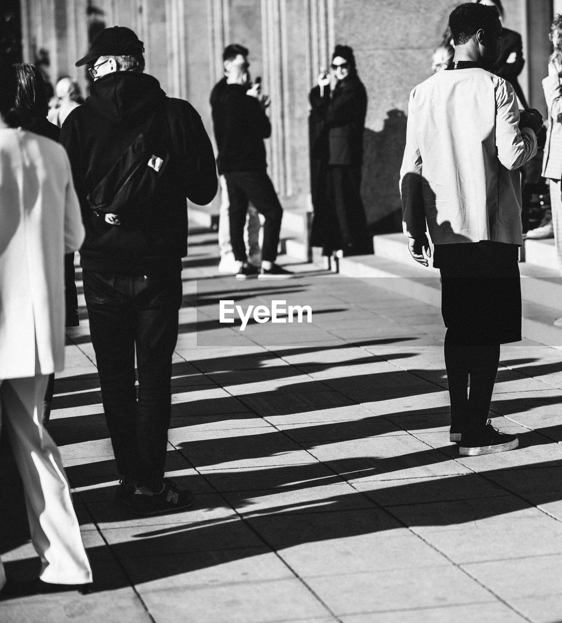 real people, group of people, full length, people, walking, lifestyles, clothing, women, adult, incidental people, men, casual clothing, day, architecture, city, rear view, standing, shadow, footpath, leisure activity