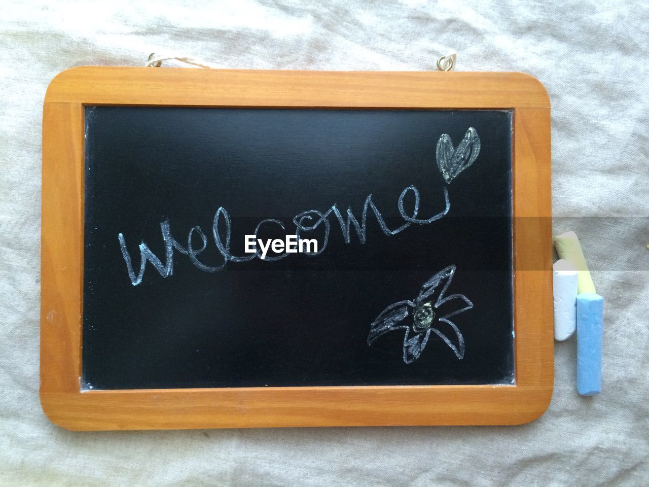 High Angle View Of Text And Flower Drawn On Slate By Chalks On Table