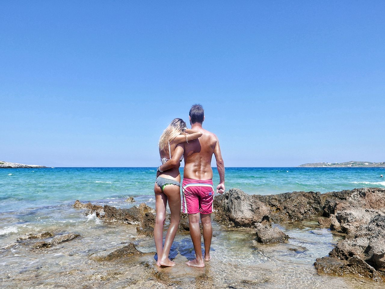 Rear view of couple standing on shore at beach against clear sky