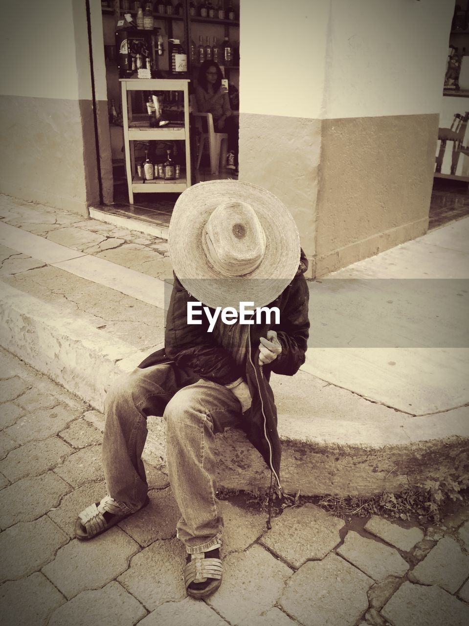 hat, real people, one person, outdoors, crouching, day, full length, casual clothing, lifestyles, sidewalk, men, sitting, people